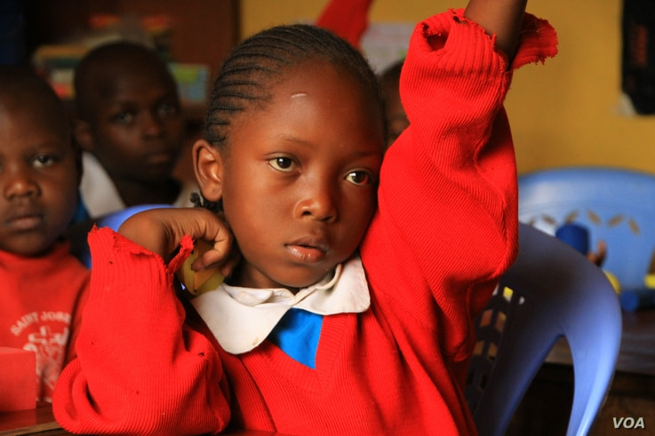 A student raises her hand to ask a question during class at the Kibera School for Girls in Nairobi, Kenya, March 19, 2013.(J. Craig/VOA)