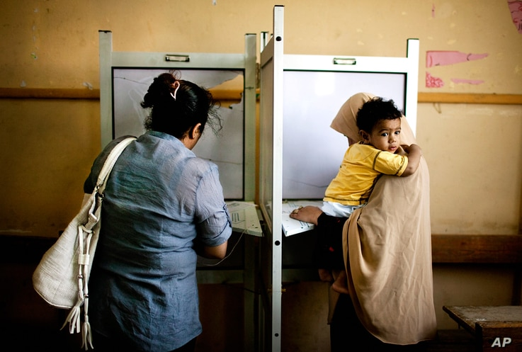 Female Egyptians cast their votes during the second day of presidential elections in the Mataraya neighborhood of Cairo, May 24, 2012.