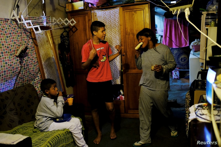 Fabiana Silva and her sons Brian, 8, left, and Breno, 14, have breakfast inside their house in Moinho favela, in Sao Paulo, Brazil, July 6, 2017.