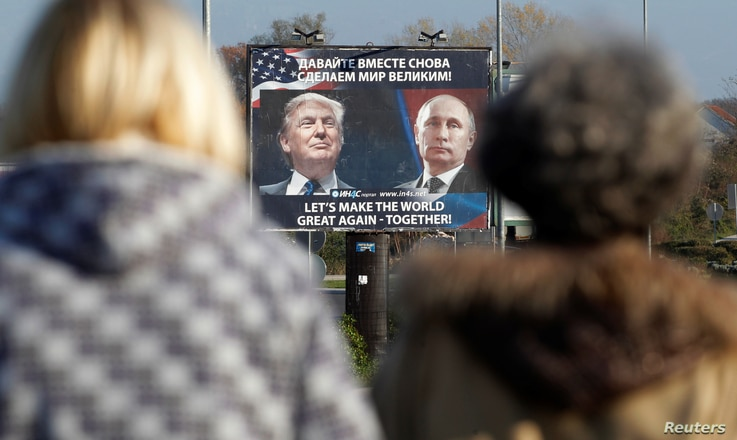 A billboard showing a pictures of US president-elect Donald Trump and Russian President Vladimir Putin is seen through pedestrians in Danilovgrad, Montenegro, Nov.16, 2016.