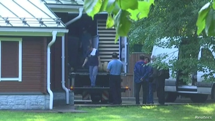 A still image taken from a video footage shows men loading a truck at a dacha compound used by U.S. diplomats for recreation, in Serebryany Bor residential area in the west of Moscow, Russia, Aug. 1, 2017.