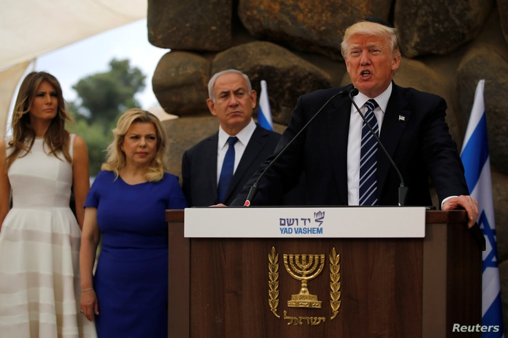 U.S. President Donald Trump, flanked by Israel's Prime Minister Benjamin Netanyahu (3rd L) and their wives Melania Trump (L) and Sara Netanyahu (2nd L), delivers remarks after a wreath-laying at the Yad Vashem holocaust memorial in Jerusalem, May 23,...