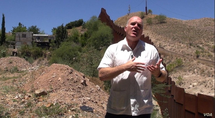Reverend Randy Mayer by the border wall in Nogales, Mexico. (G. Flakus/VOA)