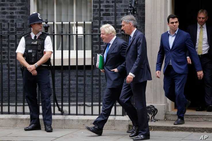 Britain Chancellor of the Exchequer Philip Hammond, center, departs with the Foreign Secretary Boris Johnson after a Cabinet meeting at 10 Downing Street in London, Sept. 21, 2017.