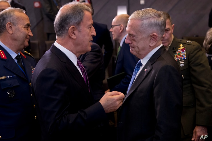 U.S. Secretary for Defence Jim Mattis, right, talks to Turkey's Defence Minister Hulusi Akar during the second day of a meeting of the North Atlantic Council at a gathering of NATO defence ministers at NATO headquarters in Brussels, Thursday, Oct. 4,...