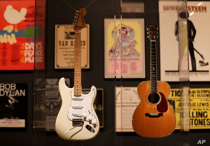 """Guitars used by Jimi Hendrix, left, and Eric Clapton are displayed with concert posters at the exhibit """"Play It Loud: Instruments of Rock & Roll,"""" at the Metropolitan Museum of Art in New York, April 1, 2019."""