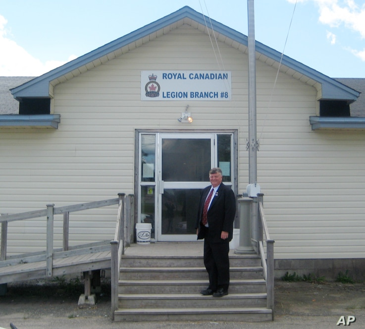 FILE - Gander, Newfoundland, Canada Mayor Claude Elliott stands in front of the Royal Canadian Legion Hall. At this remote town with a population of about 10,000 and an international airport built before World War II, 38 planes carried in 6,600 passe...