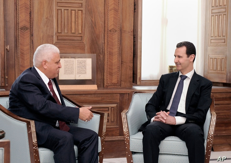 In this photo released by the Syrian official news agency SANA, Syrian President Bashar Assad, right, meets with Iraq's National Security Adviser Faleh al-Fayadth, in Damascus, Syria, May. 18, 2017.