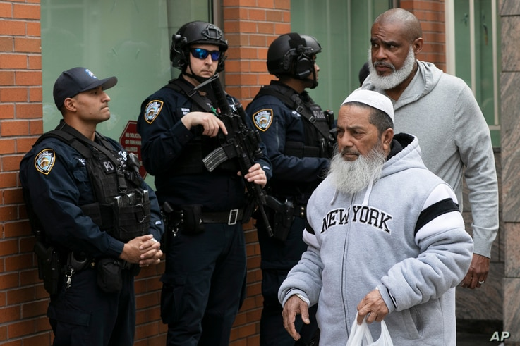 Men leave the Islamic Cultural Center of New York under increased police security following the shooting in New Zealand, March 15, 2019, in New York.