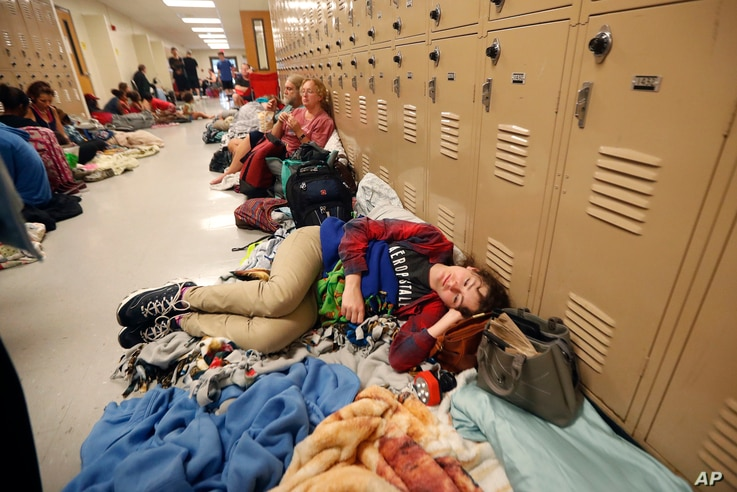 Emily Hindle lies on the floor at an evacuation shelter set up at Rutherford High School, in advance of Hurricane Michael, which is expected to make landfall today, in Panama City Beach, Fla., Oct. 10, 2018.