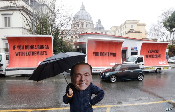 An actor wearing a mask depicting former Italian premier Silvio Berlusconi performs alongside billboards March 5, 2018, in Rome. The billboards were organised by the global civic movement Avaaz as a reaction to the right-wing coalition not reaching a...