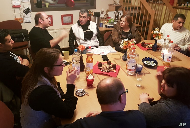 Stefan Rochow, a former far right extremist (second left) talks to refugees in Schwerin, northern Germany. Rochow works in a cafe Wednesday afternoons to help refugees from Syria and Iraq adapt to life in Germany, Nov. 30, 2016.