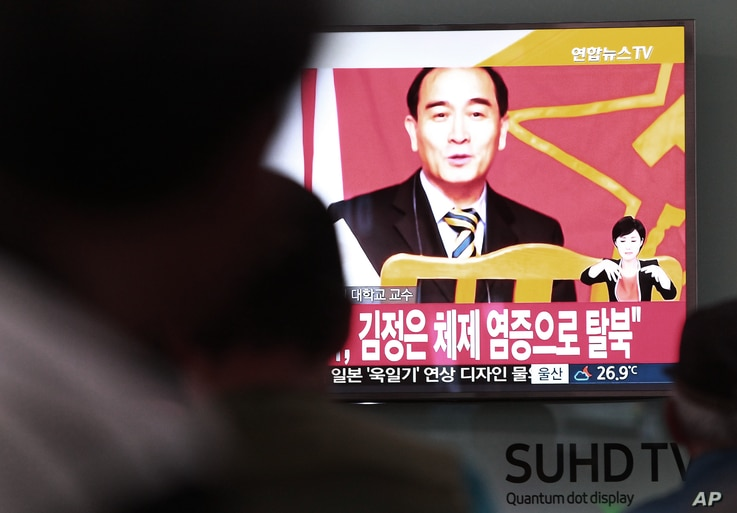 People watch a TV news showing a file image of Thae Yong Ho, minister at the North Korean Embassy in London, at Seoul Railway Station in Seoul, South Korea, Aug. 17, 2016. Thae has defected to South Korea, becoming one of the highest Northern officia...