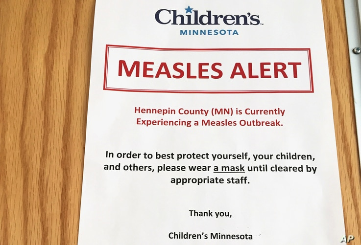 A sign at the specialty clinic at Children's Minnesota in Minneapolis alerts patients to a measles outbreak in the area, May 2, 2017.  In interviews with Somali mothers in Minnesota, VOA's Somali Service found that anti-vaccine views are widespread. ...
