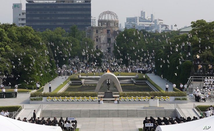 Doves fly over the cenotaph dedicated to the victims of the atomic bombing at the Hiroshima Peace Memorial Park during the ceremony to mark the 68th anniversary of the bombing, August 6, 2013.