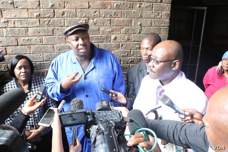 Zimbabwe's Health Minister David Parirenyatwa (right, with glasses), accompanied by local Minister Saviour Kasukuwere, talks to journalists after visiting Mbare township, the epicenter of the current typhoid outbreak in Harare, Jan. 2017. (S. Mhofu/V...