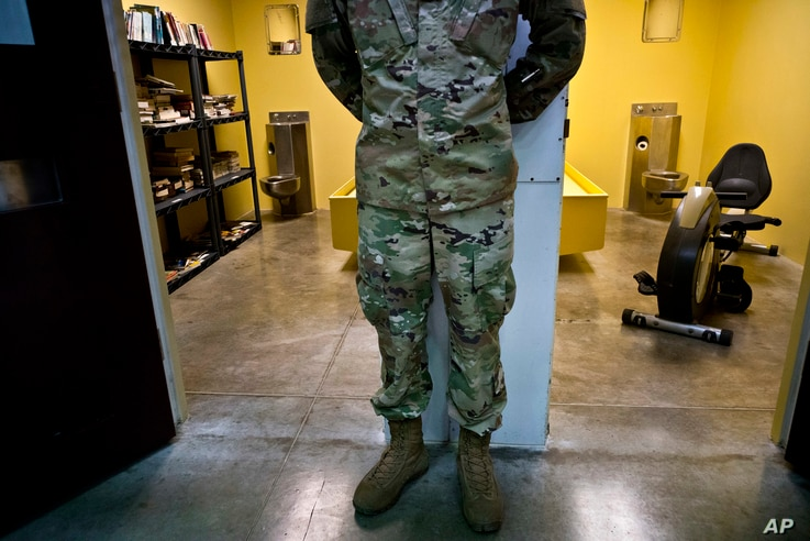 In this June 6, 2018 photo, reviewed by U.S. military officials, a guard stands between two cells, one designed as a library and the other as a gym, in Camp 6 of the Guantanamo Bay detention center, in Cuba.