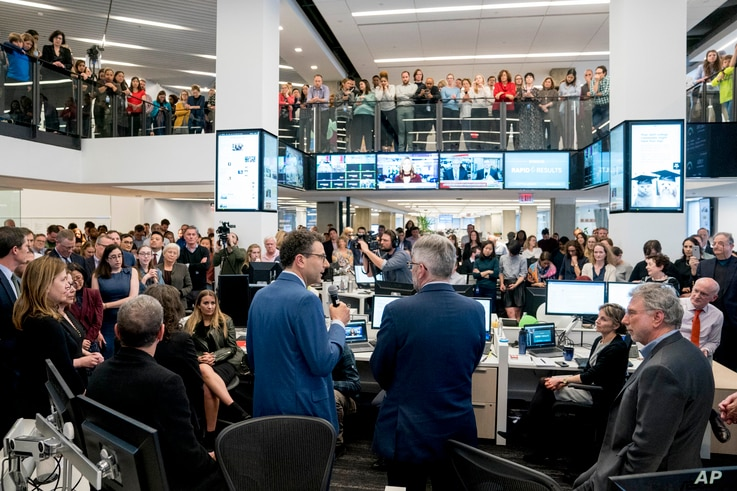 Washington Post National Politics Deputy Editor Peter Wallsten, center left, accompanied by National Security Editor Peter Finn, center right, and Executive Editor Marty Baron, right, speaks to the newsroom after The Washington Post wins two Pulitzer...