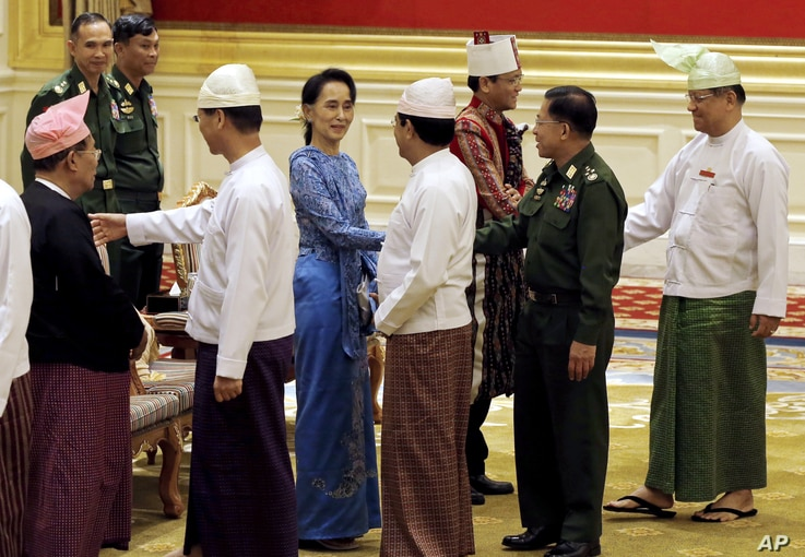 Aung San Suu Kyi, center, shakes hands with Senior General Min Aung Hlaing after the presidential handover ceremony  in Naypyitaw, Myanmar, Wednesday, March 30, 2016.