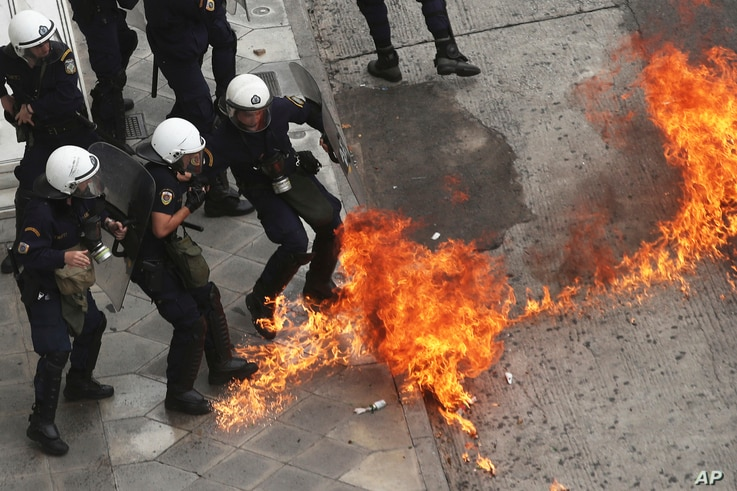 Riot police officers try to avoid a petrol bomb thrown by protester during a nationwide general strike demonstration. in Athens, May 17, 2017.