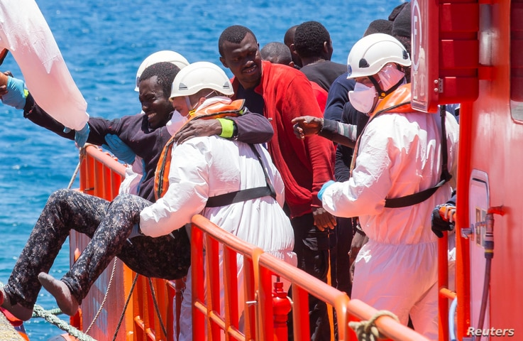 A migrant, who is part of a group of 58 intercepted aboard a makeshift boat around 100 miles off the coast, is helped by rescue workers upon arriving at Arguineguin port in the Canary Island Gran Canaria, Spain, May 30, 2016.
