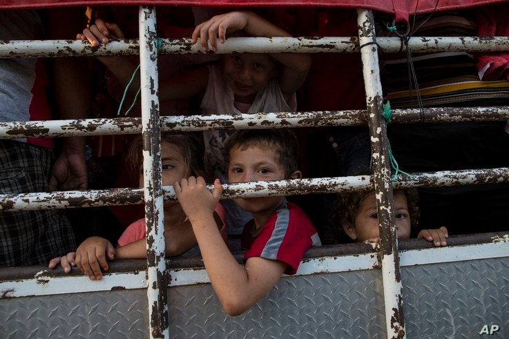 Children travel on a cattle truck, as a thousands-strong caravan of Central American migrants slowly makes its way toward the U.S. border, between Pijijiapan and Arriaga, Mexico, Oct. 26, 2018.