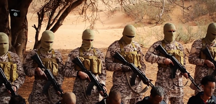 This still image from a video uploaded to social media purportedly shows Ethiopian Christians kneeling on the ground in front of masked militants from the so-called Islamic State before their execution in a desert area at an undisclosed location in L...