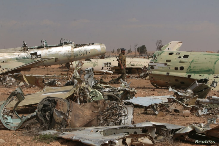 A Syrian Democratic Forces(SDF) fighter walks near destroyed airplane parts inside Tabqa military airport after taking control of it from Islamic State fighters, west of Raqqa city, April 9, 2017.