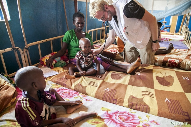 FILE -A doctor with the charity Medecins sans Frontieres (MSF) examines one of Marceline Wanou's two sons as they recover from malnutrition in a hospital in Bambari, Central African Republic, Nov. 10, 2015.