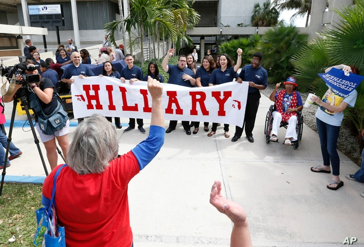 Supporters of Democratic presidential candidate Hillary Clinton cheer for a television camera as they wait for a rally to begin where Clinton and former vice president Al Gore will speak, Oct. 11, 2016, in Miami.