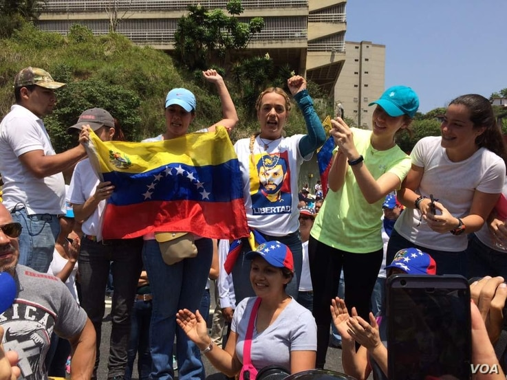 Venezuelan anti-government protesters including activist Lilian Tintori, center right in printed T-shirt, demonstrate in Caracas April 20, 2017. Tintori's shirt bears a likeness of her husband, jailed opposition leader Leopoldo Lopez. (A. Algarro/V...