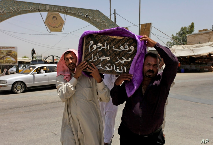 Mourners carry the coffin of a victim of violence before his burial in the Shiite holy city of Najaf, 100 miles (160 kilometers) south of Baghdad, Iraq, Tuesday, July 1, 2014. Violence has claimed the lives of 2,417 Iraqis in June, making it the dead...
