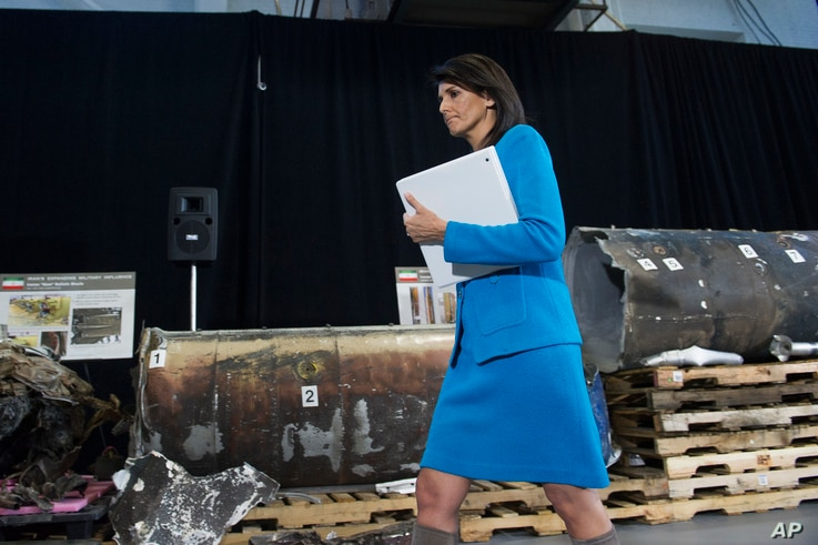 FILE - U.S. Ambassador to the U.N. Nikki Haley walks in front recovered segments of an Iranian rocket during a press briefing at Joint Base Anacostia-Bolling, Dec. 14, 2017, in Washington.
