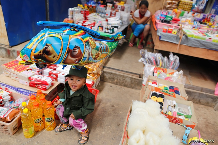 A boy dressed as United Wa State Army (UWSA) soldier, sits in a market at Mongmao, Wa territory in northeast Myanmar, Oct. 1, 2016.