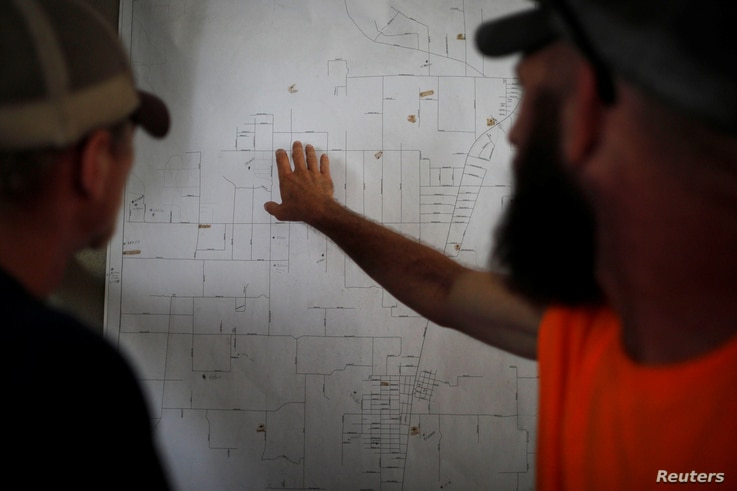 50 Star Search and Rescue team members Robert Pepper, left, and John Basehore study a map of the search area following Hurricane Michael in Youngstown, Florida, Oct. 17, 2018.