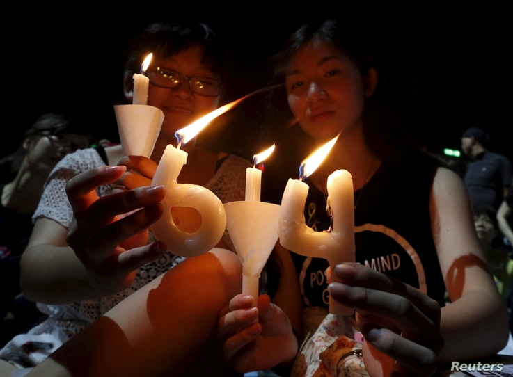 """Pro-democracy supporters hold candles in the shape of """"64"""", which symbolizes """"June 4th"""", during an annual candlelight vigil at Victoria Park in Hong Kong, China, June 4, 2015 to mark Beijing's Tiananmen Square crackdown in 1989."""