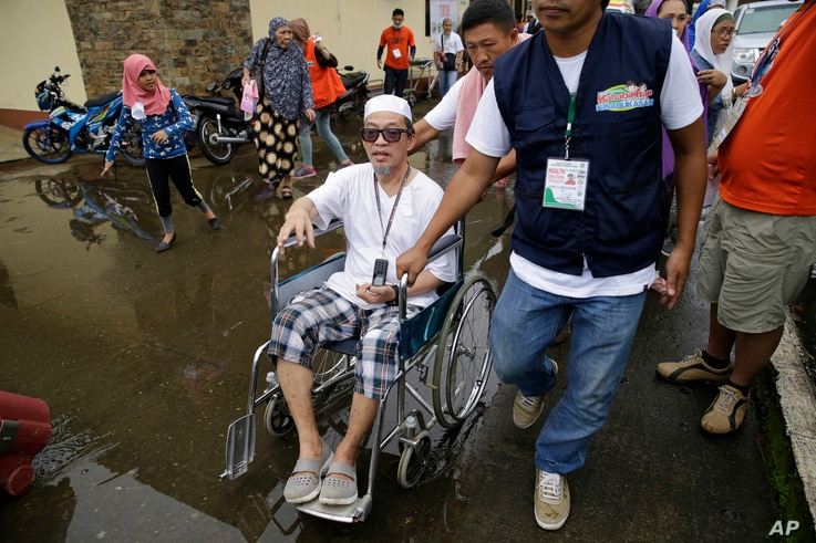 Said Salic, the husband of Rohaina Salic (center), is pushed on a wheelchair after they fled their homes in Marawi city, southern Philippines. It's unclear how many people remain trapped in Marawi. Authorities have put the figure at anywhere from 1...