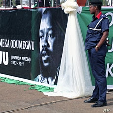 A security official stands next to a poster bearing the photograph of Biafran ex-warlord Lieutenant Colonel Odumegwu Ojukwu during a national funeral ceremony in Nigeria's southeastern city of Enugu, March 1, 2012