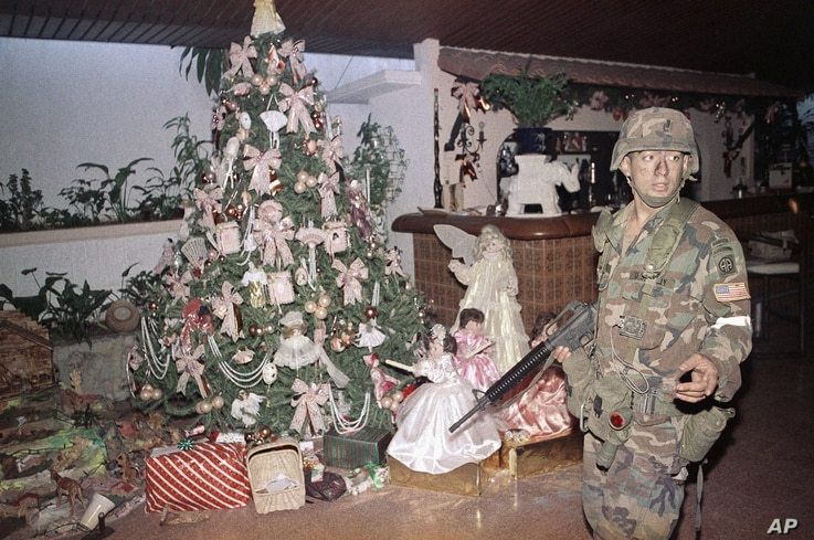 A U.S. soldier stands guard by a Christmas tree inside the house of Manual Noriega in Panama City, Dec. 23, 1989. U.S. troops are still searching for the deposed Panamanian leader.