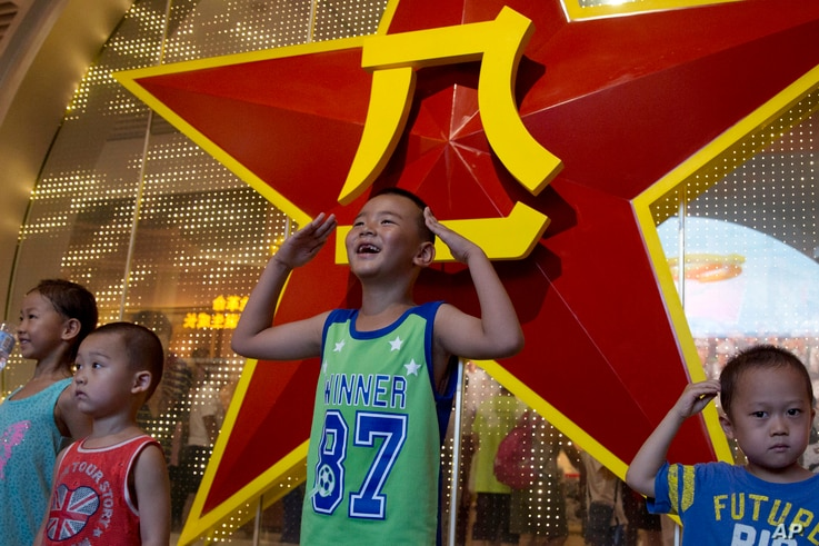A Chinese child salutes with both hands in front of the emblem of the People's Liberation Army or PLA during an exhibition to mark the 90th anniversary of the founding of the PLA at the military museum in Beijing, China, Aug. 1, 2017.