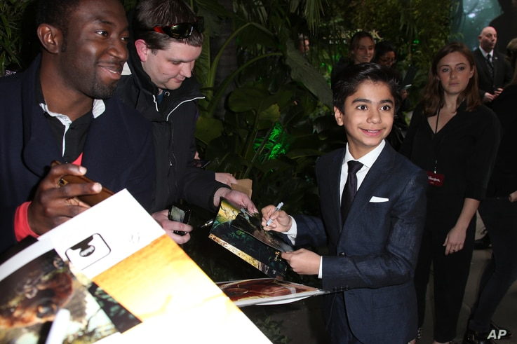 """Actor Neel Sethi, who plays the character Mowgli, signs autographs upon arrival at the premiere of the film """"The Jungle Book"""" in London, April 13, 2016."""