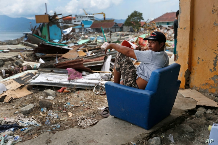 A man sits on a chair in the shell of a house heavily damaged by the tsunami in Wani village on the outskirts of Palu, Central Sulawesi, Indonesia, Oct. 4, 2018.