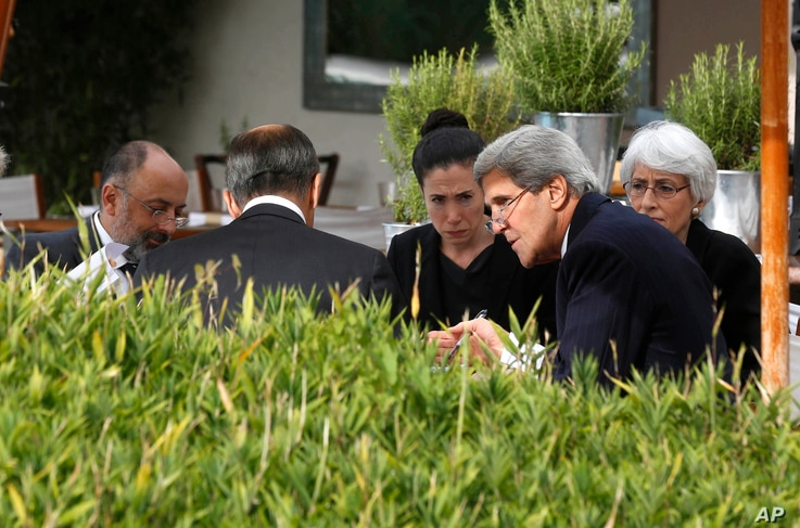 U.S. Secretary of State John Kerry, second right, and Russian Foreign Minister Sergey Lavrov, back to camera, talk, with their senior aides seated by a swimming pool at a hotel in Geneva Switzerland, Sept. 14, 2013.
