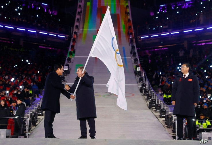 International Olympic Committee President Thomas Bach, center, receives the Olympic flag from Sim Jae-guk, left, the mayor of Pyeongchang, during the closing ceremony of the 2018 Winter Olympics in Pyeongchang, Feb. 25, 2018.