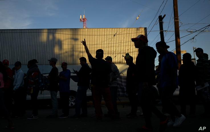 Men line up for dinner outside a shelter housing members of the migrant caravan,  in Tijuana, Mexico, Nov. 26, 2018.