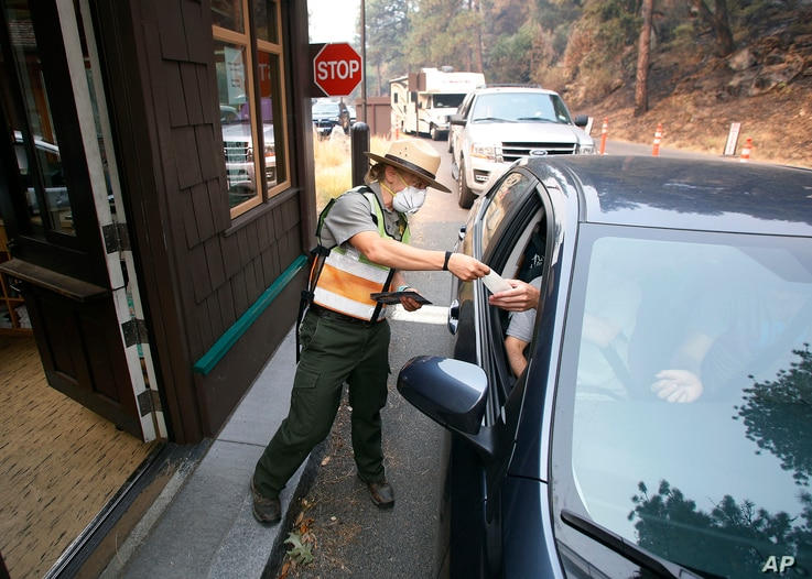 Park Ranger Anne Simmons passes maps out and directs visitors at the Hwy 140 gate as Yosemite National Park reopens after a three week closure from smoke and fires that led to most tourists canceling their trips, Aug. 14, 2018 in Yosemite, Calif.