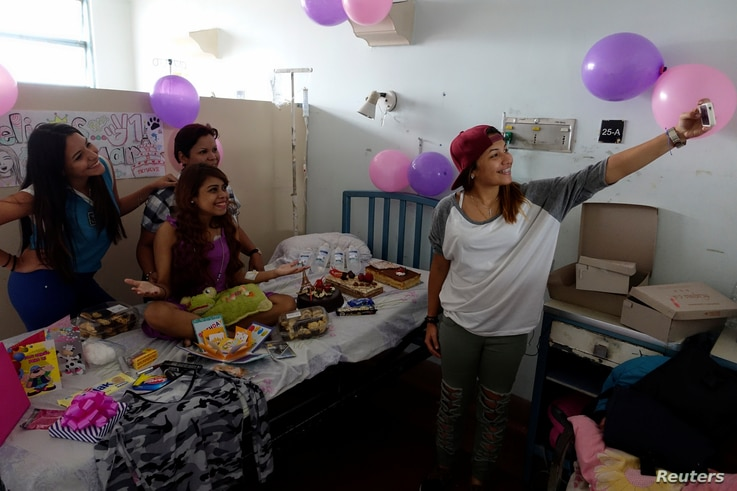 Lismar Castellanos, 21, who lost her transplanted kidney, takes a selfie with her mother and friends during her birthday celebration at a state hospital in Caracas, Venezuela, Feb. 7, 2018.