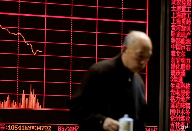 A man walks past an electronic board displaying stock prices at a brokerage house in Beijing, Monday, Jan. 11, 2016.