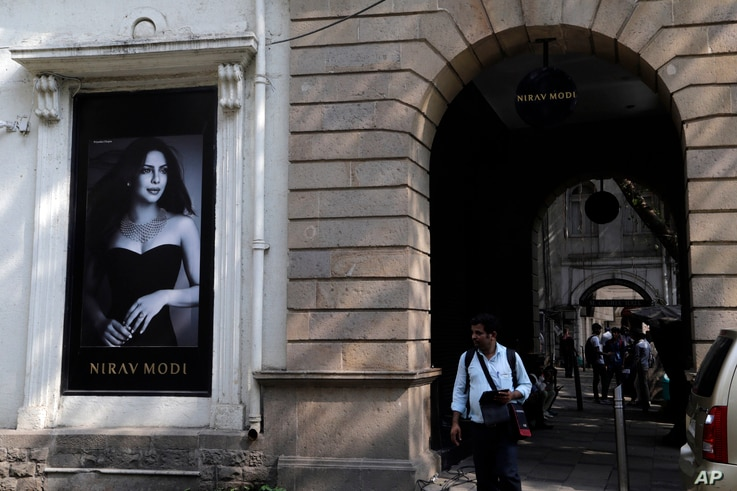 A man walks in front of a Nirav Modi jewelry boutique, that displays a black and white photograph of Bollywood actress Priyanka Chopra in Mumbai, India, Feb. 15, 2018.