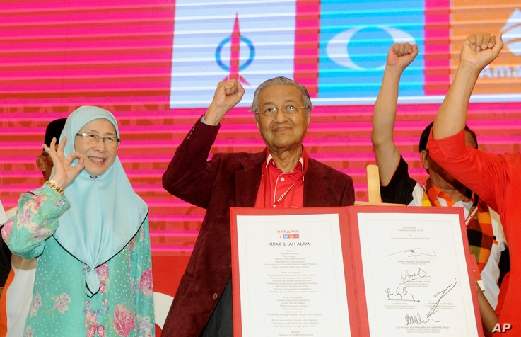 Malaysia former Prime Minister Mahathir Mohamad, center, and Wan Azizah, wife of former Deputy Prime Minister Anwar Ibrahim, wave during a political opposition alliance meeting in Shah Alam, Malaysia, Jan. 7, 2018.